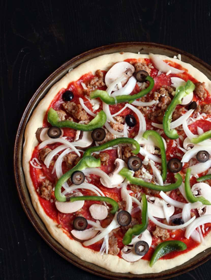 This image has an empty alt attribute; its file name is pizza-before-baking.jpg