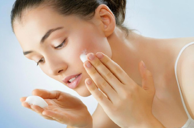 woman-in-white-tank-putting-face-cream-on-face